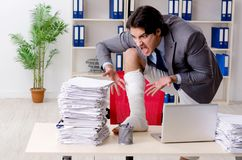 The leg injured employee working in the office. Leg injured employee working in the office royalty free stock photos