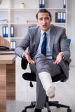 The leg injured male employee in the office. Leg injured male employee in the office stock image