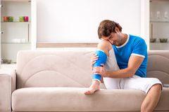 The leg injured young man on the sofa royalty free stock image