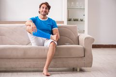The leg injured young man on the sofa stock images