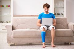 The leg injured young man on the sofa stock photos