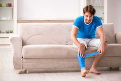 The leg injured young man on the sofa royalty free stock photos