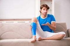 The leg injured young man on the sofa royalty free stock images