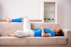 The leg injured young man on the sofa royalty free stock photography