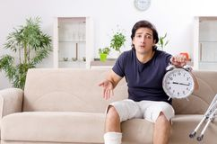 The leg injured young man suffering at home. Leg injured young man suffering at home stock photo