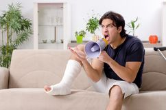 The leg injured young man suffering at home. Leg injured young man suffering at home stock photos
