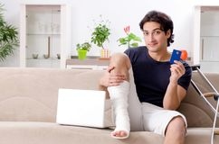 The leg injured young man suffering at home. Leg injured young man suffering at home royalty free stock photos