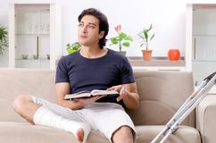 The leg injured young man suffering at home. Leg injured young man suffering at home royalty free stock photography