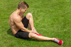 Leg injury during excercise. Man holding his ankle after injury during excercise Royalty Free Stock Photo