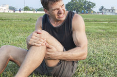 Leg injury. Man suffers painful hamstring injury and holds painful area with hands as he sits on grassy ball field stock photography