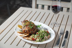 Leg of lamb baked with sauce in the white plate closeup with a side dish of rice. Rustic wooden table and a glass of red wine. Stock Photography