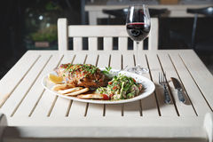 Leg of lamb baked with sauce in the white plate closeup with a side dish of rice. Rustic wooden table and a glass of red wine. Royalty Free Stock Photo