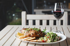 Leg of lamb baked with sauce in the white plate closeup with a side dish of rice. Rustic wooden table and a glass of red wine. Leg of lamb baked with sauce in stock image