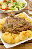 Leg of lamb roast. Roast leg of lamb with rosemary and garlic,  served with baked potatoes Stock Image