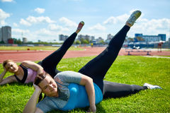 Leg lifting. Small group of plus-size females lying on grass and lifting stretched legs Stock Photo