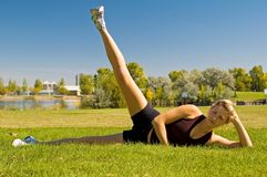 Leg lifts. Young woman doing leg lifts in a park Stock Images
