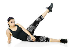 Leg Lifts. A pretty teen girl looking at the viewer as she performs side-lying leg lifts in her exercise outfit.  On a white background Stock Images