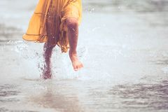 Leg of little child girl running on beach with water splashing. In summer vacation in vintage color tone royalty free stock images
