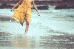 Leg of little child girl running on beach with water splashing. In summer vacation in vintage color tone royalty free stock image