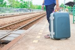 Leg male of travel put jeans stand and suitcase wait train in station  trail platform with copy space.  Stock Image