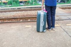 Leg male of travel put jeans stand and suitcase wait train in station  trail platform with copy space.  Royalty Free Stock Photography