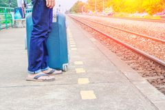 Leg male of travel put jeans stand and suitcase wait train in station  trail platform with sunset light and copy space.  Royalty Free Stock Images