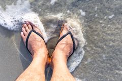 Leg of the male with wear flip flops while standing on the beach. The swash of seawater up the beach. selective focuse Stock Photography