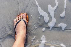 Leg of the male with wear flip flops while standing on the beach. The swash of seawater up the beach Stock Photos