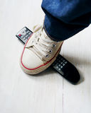 Leg of the man step on the television panel. Concept of active lifestyle, hobby. Concept against television propaganda. Appeal to uncover manipulation Royalty Free Stock Image