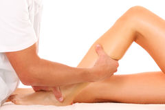 Leg massage. A picture of a physio therapist trying to fix the leg over white background royalty free stock photography