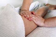 Leg massage. Male masseur therapist hands doing applying pressure kneading on female calf . Professional masseuse massaging foot of girl. Woman having sports Royalty Free Stock Image