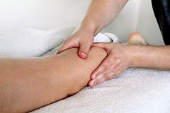 Leg massage. Male masseur therapist hands doing applying pressure kneading on female calf . Professional masseuse massaging foot of girl. Woman having sports stock photography