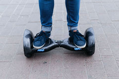 Leg men in sneakers and jeans standing on the blue platform. Start to using the electrical scooter, hoverboard or gyroscooter. Stock Image