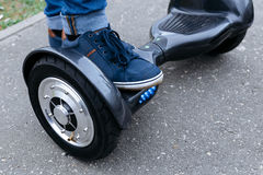 Leg men in sneakers and jeans standing on the blue platform. Start to using the electrical scooter, hoverboard or gyroscooter. Leg men in blue sneakers and Stock Images