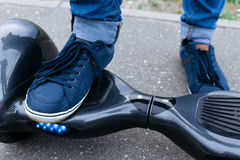 Leg men in sneakers and jeans standing on the blue platform. Start to using the electrical scooter, hoverboard or gyroscooter. Leg men in blue sneakers and Royalty Free Stock Image