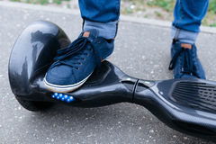 Leg men in sneakers and jeans standing on the blue platform. Start to using the electrical scooter, hoverboard or gyroscooter. Leg men in blue sneakers and Royalty Free Stock Photo