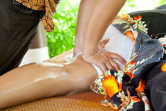 Leg Oil Massage Spa. Oil Massage Spa at leg by Hand in tropical garden for wellness and healthy background stock photography