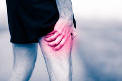 Leg pain, man holding sore and painful muscle. Runners leg pain on workout. Man holding sore and painful leg muscle, sprain or cramp ache filled with red pink Stock Image