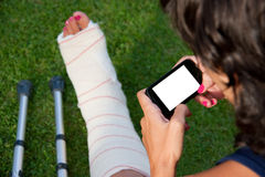 Leg in plaster and blank screen smart phone Royalty Free Stock Image