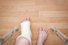 Leg in plaster and crutches Royalty Free Stock Photo