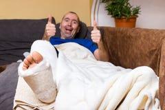 Leg in plaster. Man lying with a broken leg on sofa Royalty Free Stock Photo