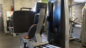 Leg press sitting equipment in sport gym. Empty leg press sitting equipment in sport gym. Back shot of black leg press sitting sport equipment with beige seats stock photo