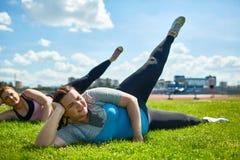 Leg raiisng. Two plus-size females raising legs during workout on lawn Royalty Free Stock Images