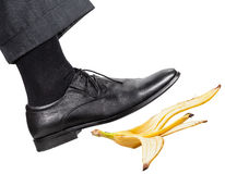 Leg in the right black shoe slips on a banana peel Royalty Free Stock Photography