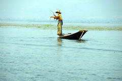 Leg rowing fisherman and his nets. In a small boat on Inle Lake,  Myanmar (Burma Stock Photography