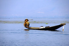 Leg rowing fisherman and his nets. In a small boat on Inle Lake,  Myanmar (Burma Royalty Free Stock Image