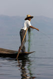 Leg-rowing fisherman at Inle Lake, Myanmar. The photo shows a leg-rowing fisherman at Inle Lake, a famous tourist destination in Myanmar. Leg-rowing with one leg Stock Images