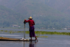 Leg-rowing fisherman at Inle Lake, Myanmar. The photo shows a leg-rowing fisherman at Inle Lake, a famous tourist destination in Myanmar. Leg-rowing with one leg Royalty Free Stock Photos