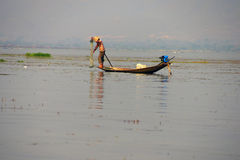 Leg rowing fisherman sets his nets Royalty Free Stock Images
