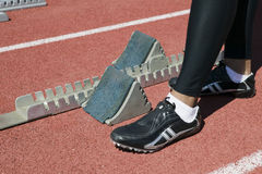 Leg's Of Male Athlete At Starting Block. Low section of male athlete at starting block on racetrack Stock Image